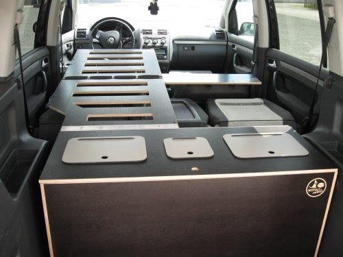 Les kit Nomad Addict permettent de transformer et aménager votre véhicule voiture ou fourgon en mini camping-car. C'est la solution idéale pour installer un lit, camper et dormir dans sa voiture ou son fourgon aménagé. Nos kits de camping pour voiture sont entièrement amovibles en quelques minutes. Le Kit Duo ici dans un Volkswagen Touran